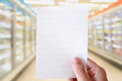 Hand hold white paper over supermarket aisle blur background. Hand hold white paper over supermarket aisle with refrigerators blurred background Royalty Free Stock Photos