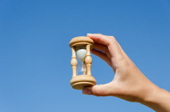 Hand hold wooden hourglass on blue sky background Stock Photo