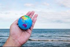 Hand hold worldlandscape ocean sky horizental line Stock Image