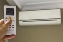 Hand holdind control switch of home air conditioner.  Stock Photo