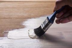 Free Hand Holding A Brush Applying Varnish Paint Royalty Free Stock Photography - 47207967