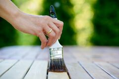 Free Hand Holding A Brush Applying Varnish Paint On A Wooden Garden Table - Painting And Caring For Wood With Oil Royalty Free Stock Images - 213654809