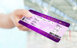 Hand holding air ticket on airport Stock Image