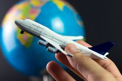 Air travel around the world. Hand holding airplane flying around the globe over black background Stock Images
