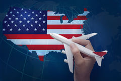 Hand holding airplane with map of USA. Stock Photos