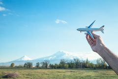 Hand holding airplane model in front of Ararat mountain background. Travel, Armenia royalty free stock photos