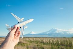 Hand holding airplane model in front of Ararat mountain background. Travel, Armenia stock photography
