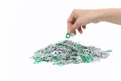 Hand holding aluminum cap can over a pile of cap can Royalty Free Stock Photo