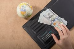 Hand holding American dollar  on wooden background. Hand holding American dollar  banknotes beside a globe Stock Photography