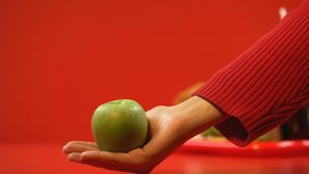 Hand holding apple, fast food on background, concept of healthy nutrition choice. Stock footage stock footage