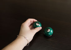 Hand holding a ball and another ball on a table Royalty Free Stock Photography