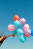 Hand holding balloons sky background Stock Photo