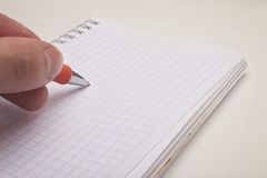 Hand holding a ballpoint pen and notepad Royalty Free Stock Images