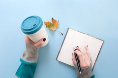 Hand holding bamboo reusable takeaway cup with lid on and writing on blank pages of notebook, on blue background.  royalty free stock photos