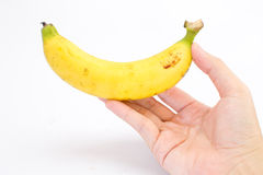 Hand is holding a banana. Isolated on white background Royalty Free Stock Photography