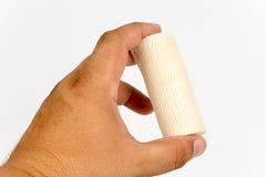 Hand holding bandage roll over white background Stock Photo