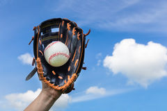 Hand holding baseball in glove with blue sky. Female hand holding baseball in glove with blue sky royalty free stock image