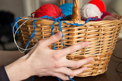 Hand holding a basket   with knitting needles and balls of wool. Hand holding a basket with colorful balls of wool Stock Images