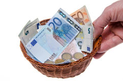 Hand holding a basket full of money Royalty Free Stock Photography