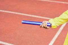 Hand holding baton for relay.  stock image