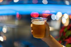 Hand holding beer glass on abstract background royalty free stock images