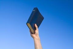 Hand Holding Bible. Over blue sky Stock Images