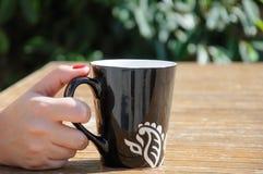 Hand holding big black coffee mug Stock Image