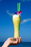 Hand Holding A Big Glass Of Cocktail. On A Deep Blue Water And Sky Background Royalty Free Stock Images