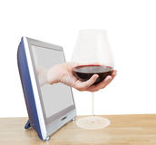 Hand holding big glass with red wine leans out TV Stock Images