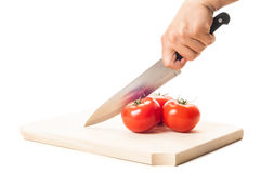 Hand holding a big knife, three tomatoes and wooden board Stock Photos