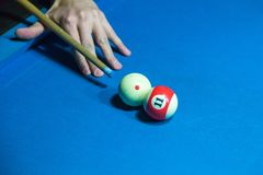 Hand holding billiard stick cue on a pool table ready to shot ball. Hand holding billiard stick cue on a pool table ready to shot the ball Royalty Free Stock Photos