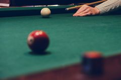 Hand holding billiard stick cue ready to shot ball. Hand holding billiard stick cue on a pool table ready to shot the ball royalty free stock photo