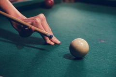 Hand holding billiard stick cue ready to shot ball. Hand holding billiard stick cue on a pool table ready to shot the ball stock image