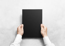 Hand holding black blank paper sheet mockup, isolated. Royalty Free Stock Images