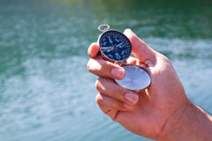 Hand holding the black compass Royalty Free Stock Image