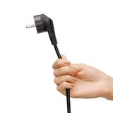 Hand holding black electrical plug with wire Stock Photography