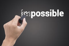 Hand holding black eraser changing the word impossible Stock Image