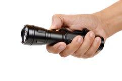 Hand holding a black flashlight stock photos
