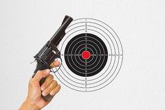 Hand holding black gun with shooting target background. Sport concept Stock Image