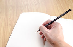 Hand holding black pencil writting on blank open notebook on woo Royalty Free Stock Image