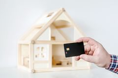 Hand holding black plastic chip card. Wooden house model on background. Wire payment transfer. Cashless money transaction.  stock images