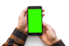 Hand holding black smartphone with green screen for chroma key compositing isolated on white background. Hand holding black smartphone with green screen for Royalty Free Stock Photos