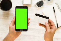 Hand holding black smartphone with green screen for chroma key compositing Online payments plastic card Smartphone with green. Hand holding black smartphone with stock image