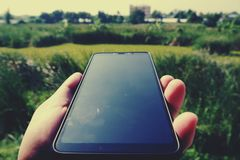 Hand holding black smartphone with black screen against blurred garden background stock image