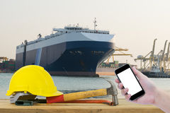 Hand holding the black smartphone with Yellow Safety Helmet on f Stock Image