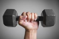 Hand holding black steel dumbbell Stock Image