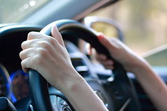 Hand holding on black steering wheel while driving Stock Photography