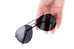 Hand holding black sunglasses Royalty Free Stock Photos