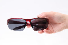 Hand holding black sunglasses. On white background Royalty Free Stock Image