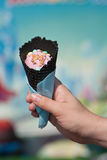Hand holding  black waffle cone with pink ice cream on a bright colored background. Royalty Free Stock Photo